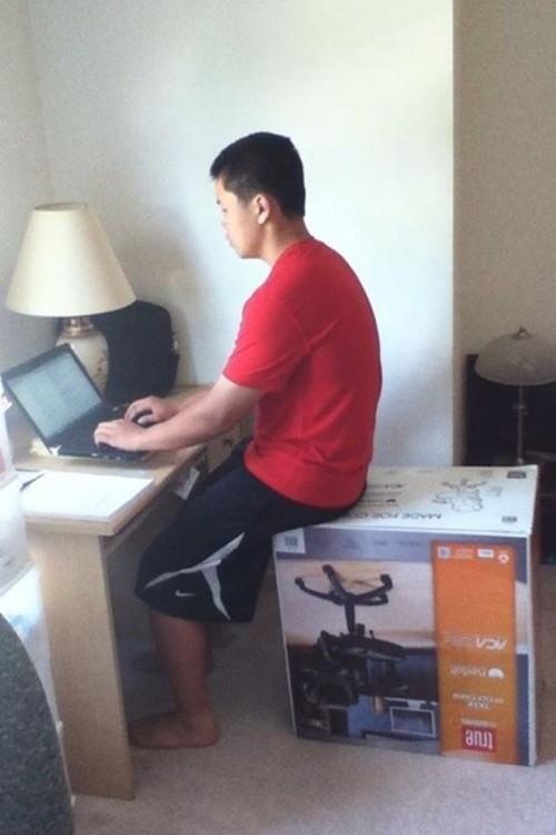 un chico sentado sobre una caja de una silla de escritorio