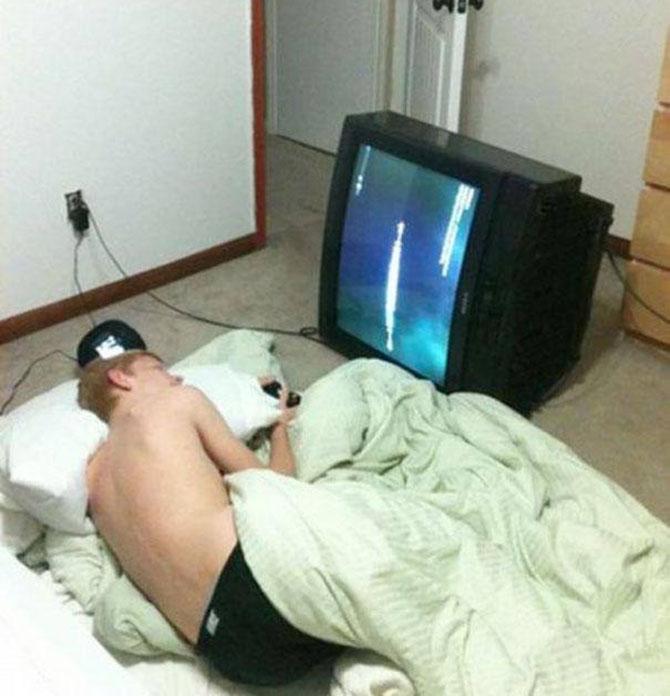 chico acostado en el suelo viendo la televisión acostada de lado