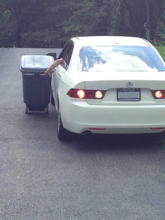 persona llevando un bote de basura desde la venta de un coche
