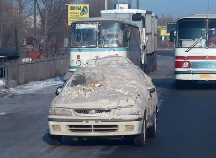 coche lleno de nieve transitando por una calle