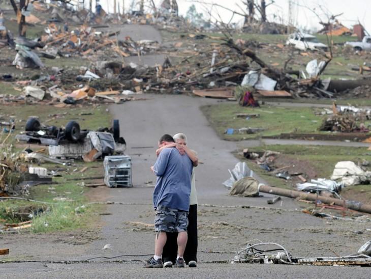 Madre abrazando a su hijo cerca de su casa destrozada después de una tragedia