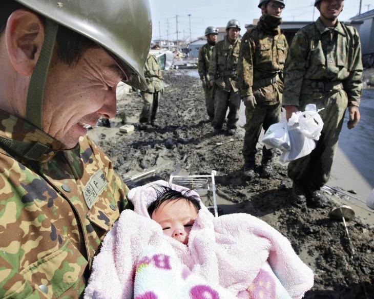 foto de un soldado con una bebé recién rescatada de entre los escombros durante un tsunami en Japón
