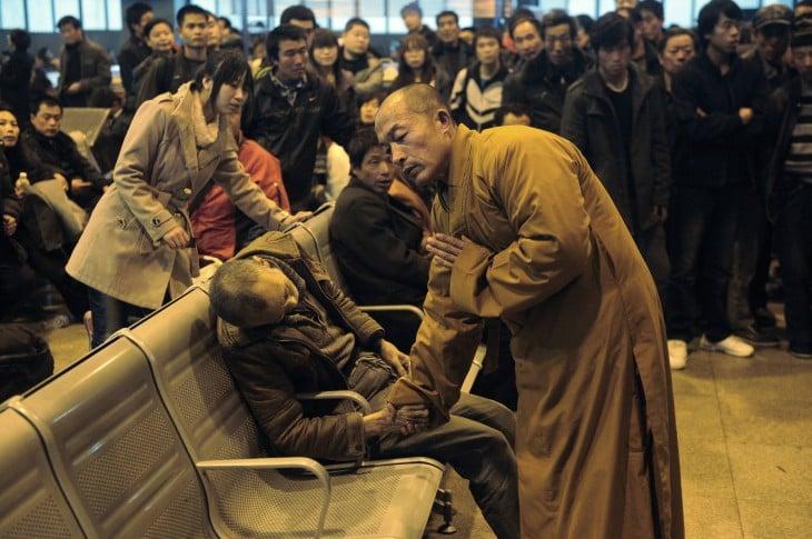 monje rezando a un hombre muerto dentro de una estación de tren en China