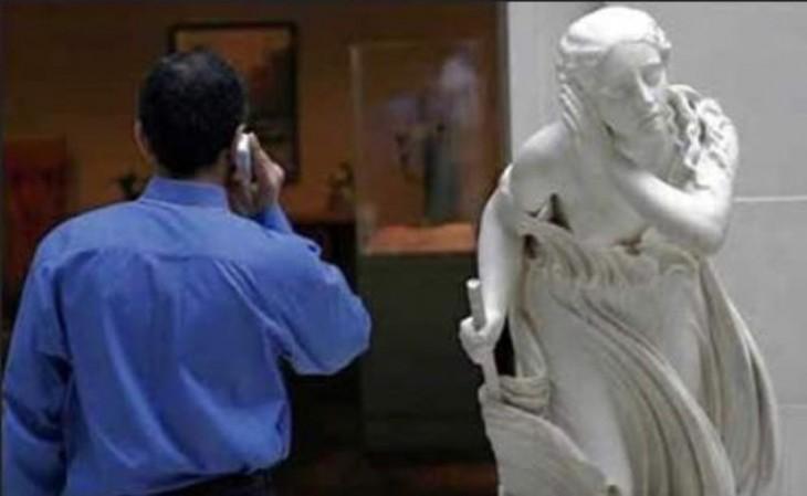 foto de un hombre hablando por teléfono a un lado de una estatua que parece que lo va a escuchar