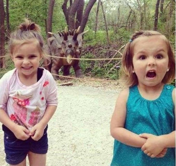 gemelas posando para la foto con el dinosaurio de atrás