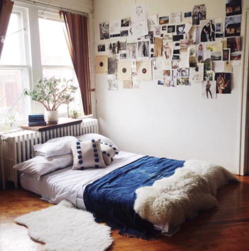 un colchón en el suelo en una recámara con muchas fotos pegadas en la pared