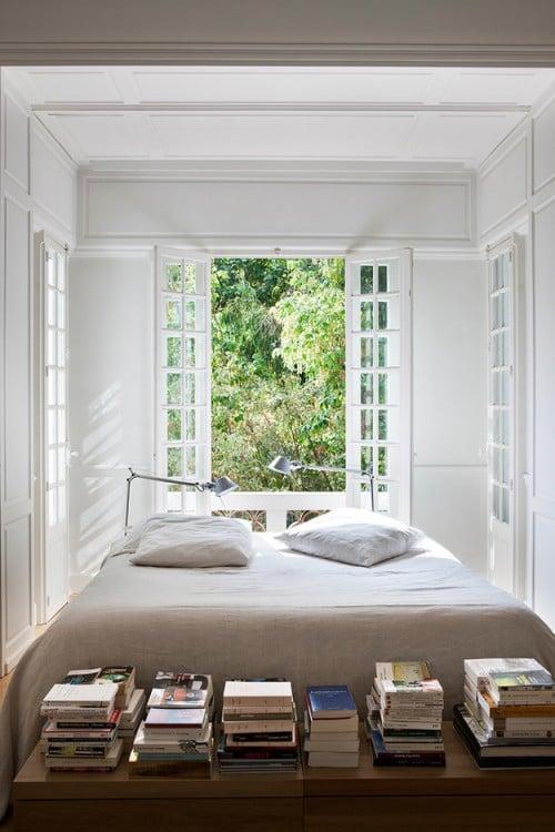 recámara con una cama rodeada de ventanales en color blanco y una base con libros al pie de la cama
