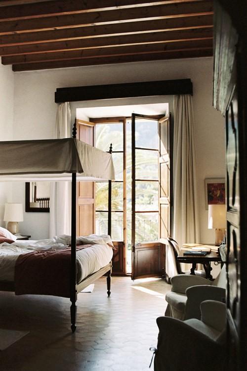 habitación con una cama que tiene protección en la parte superior, sillones y una mesa de trabajo cerca de una ventana