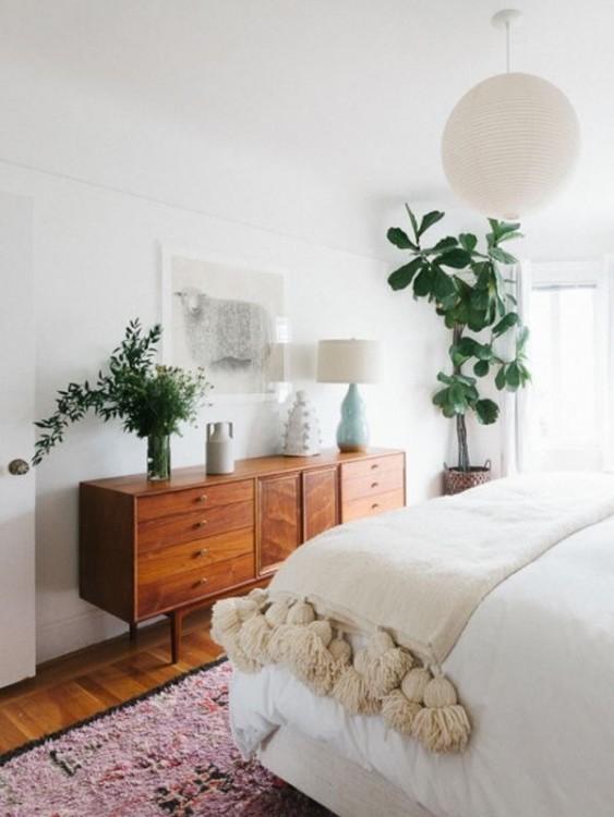 habitación donde solo se ve una parte de la cama y un mueble con unas plantas