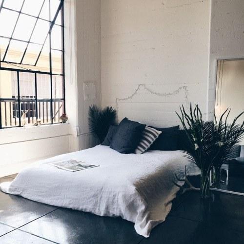 recámara con una cama cerca de una ventana con unas plantas a sus lados y pintada en color blanco