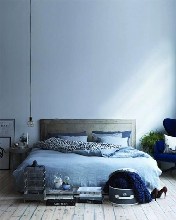 habitación con una cama en color azul y un pequeño foco colgando del techo