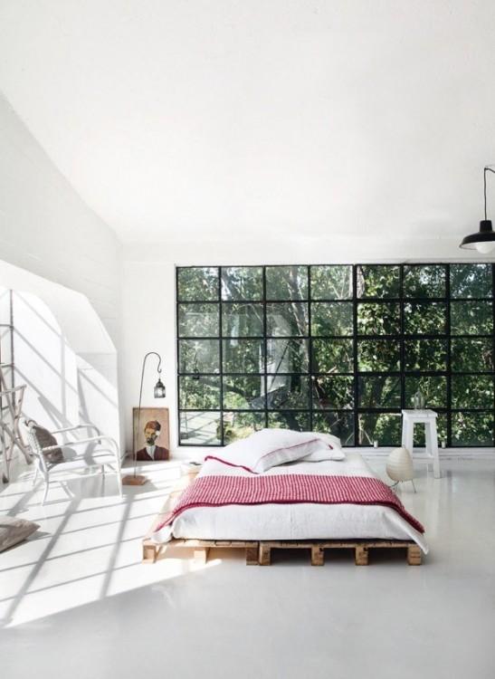 recámara vintage con una cama sobre bases de madera y un color blanco rodeada de muy pocas cosas