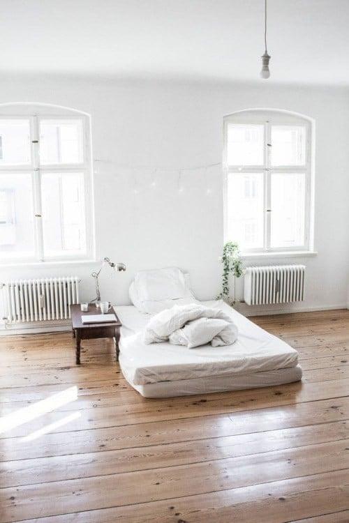 recámara de color blanco con una pequeña cama individual en sábanas blancas