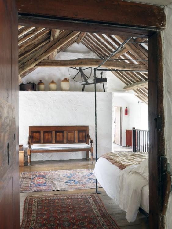 habitación rústica que parece ser de adobe con muebles de madera