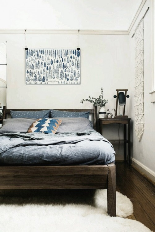 cama dentro de una habitación en color blanco con un cuadro encima de la cama