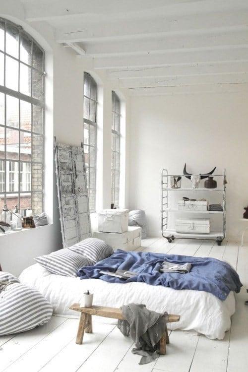 Recámara en color blanco con un pequeño colchón en el suelo y herramientas de pinturas a su alrededor