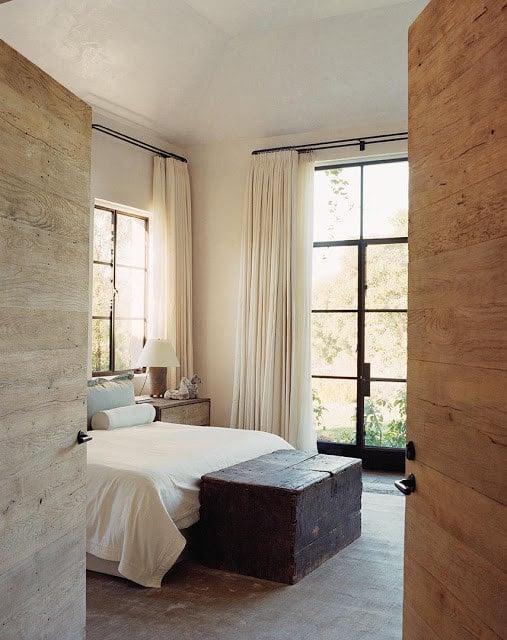 habitación rodeada de ventanas con una cama matrimonial que a los pies tiene un cofre