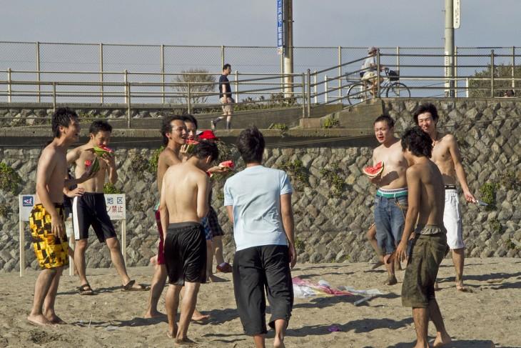 chicos Japoneses comiendo sandía en una playa