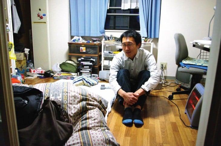 Hombre japones sentado en el suelo de tu habitación