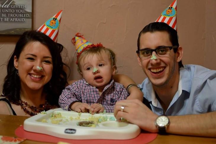 una pareja de esposos festejando a su hijo con un pastel
