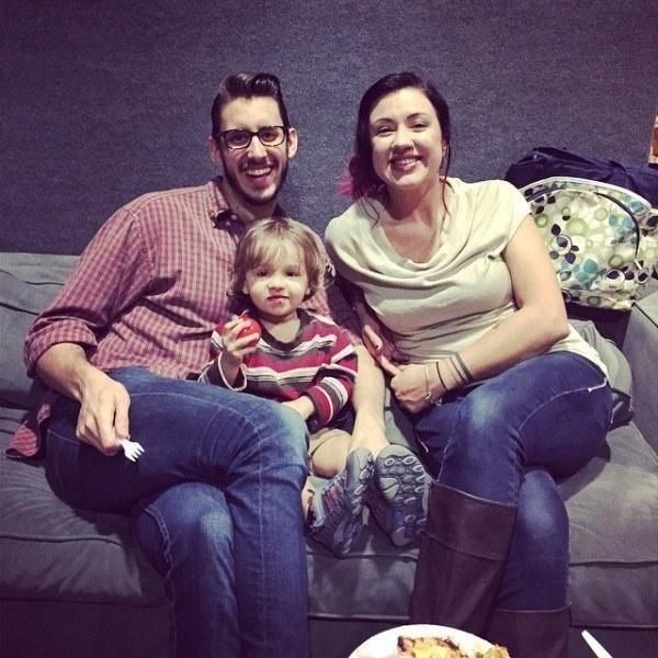 una pareja de esposos con su bebé en medio sentados en un sillón