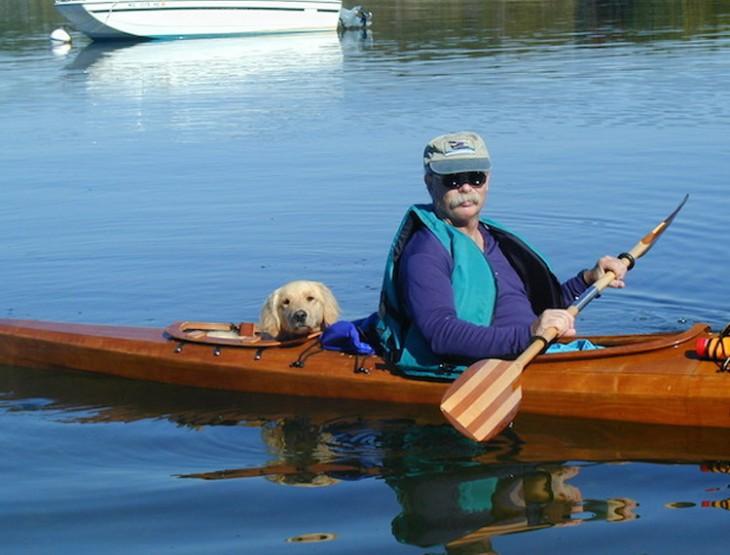 foto de un hombre y un perro dentro de un kayak en un lago