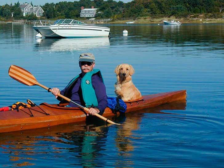 hombre dentro del kayak con un perro detrás