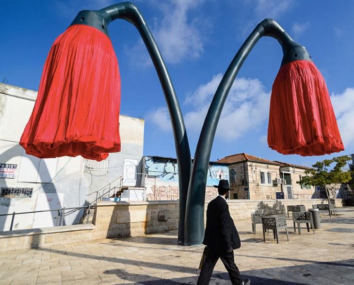hombre caminando en la plaza Varsello de Jerusalén cerca de las lámparas de flores rojas