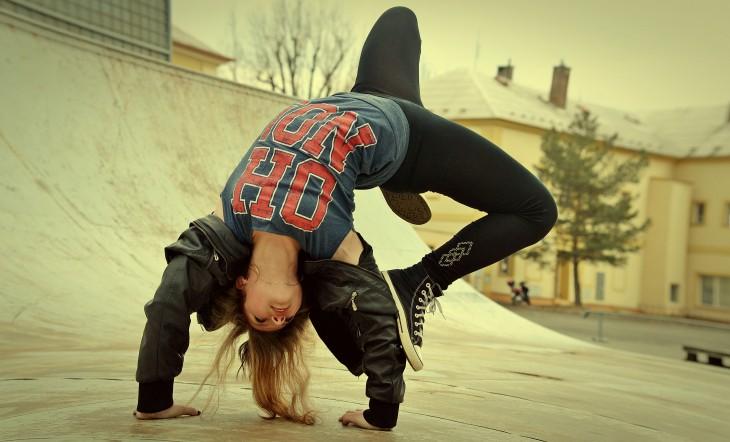 una chica bailando break dance en una calle