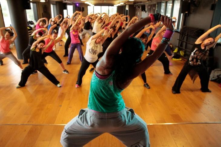 instructora de baile haciendo estiramiento frente a sus alumnas