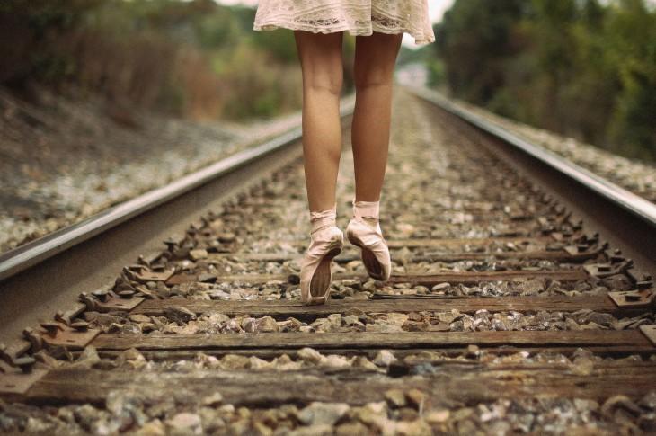 pies de una bailarina de ballet a la mitad de unas vías de ferrocarril
