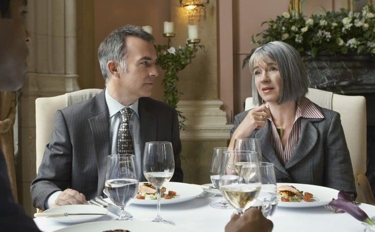 un hombre y una mujer elegantes sentados ante una mesa durante una cena