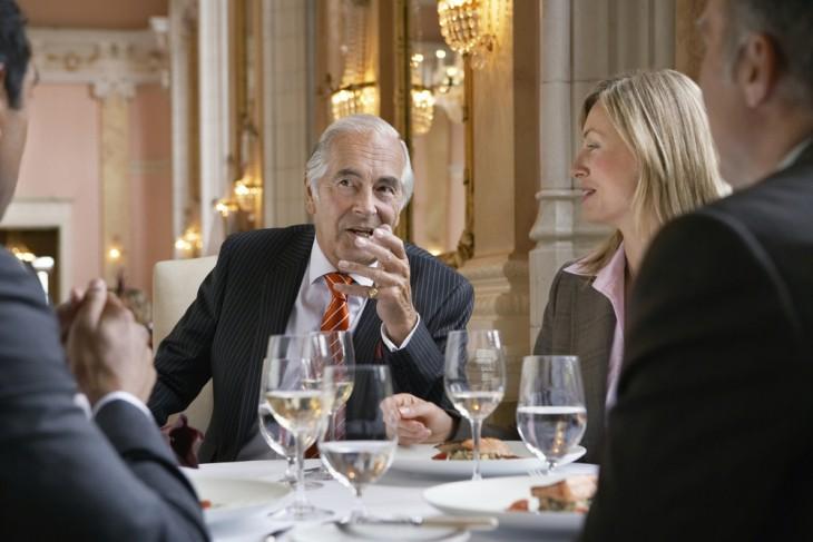 hombre hablando durante una cena rodeado de personas