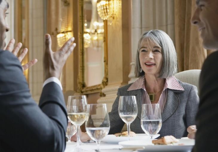 personas platicando durante una cena y la cara de una mujer sonriendo