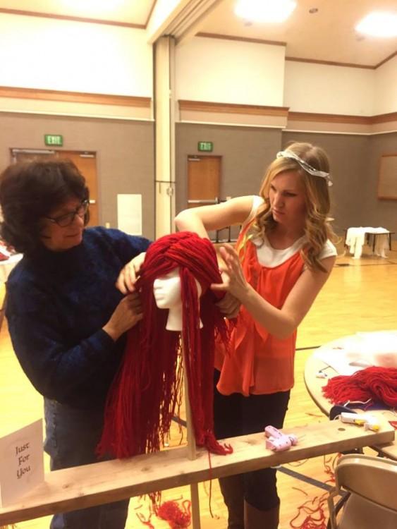 """Dos mujeres preparando una peluca de Ariel """"La Sirenita"""""""