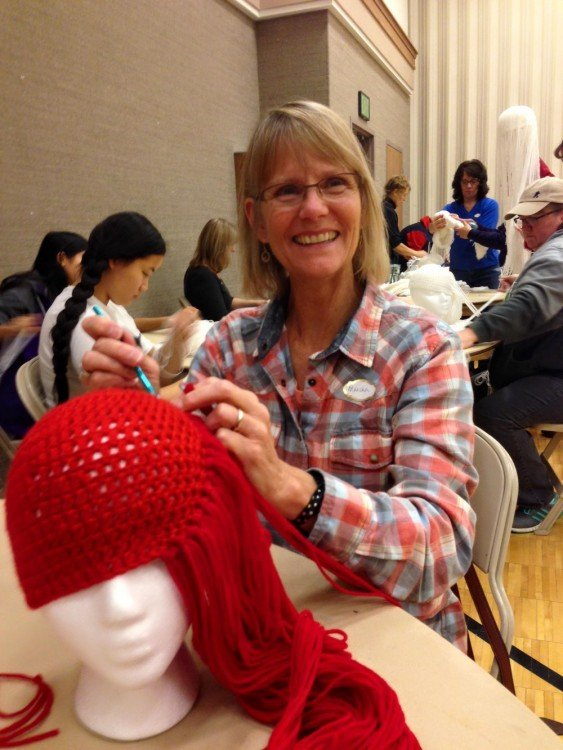 mujer tejiendo una peluca con hilo en color rojo