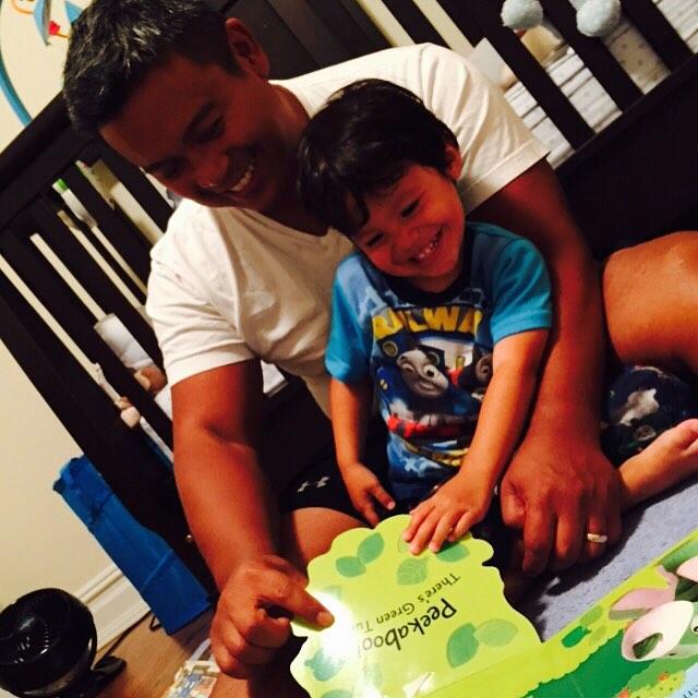 hombre leyendole a su pequeño