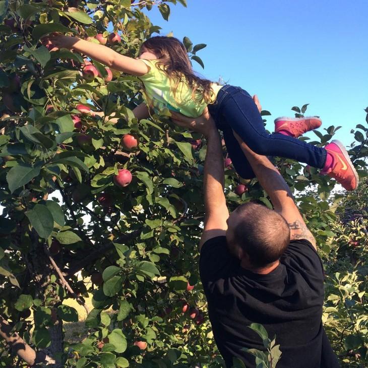 papa ayudando a cortar manzanas a su hija