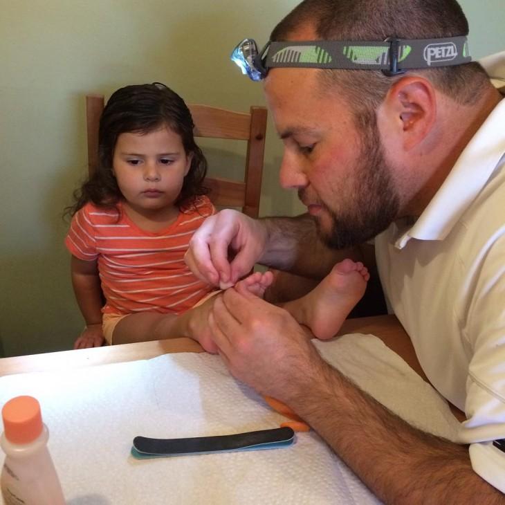 papa cortandole las uñas a su hija