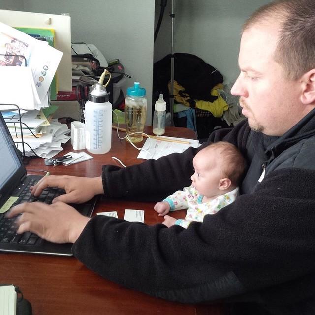 papa trabajando mientras cuida a su bebé