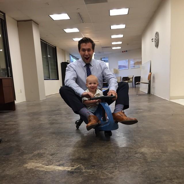 papa jugando al carrito con su hijo en la oficina