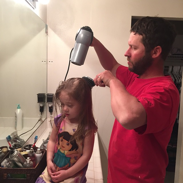 papa secandole el cabello a su niña en el baño