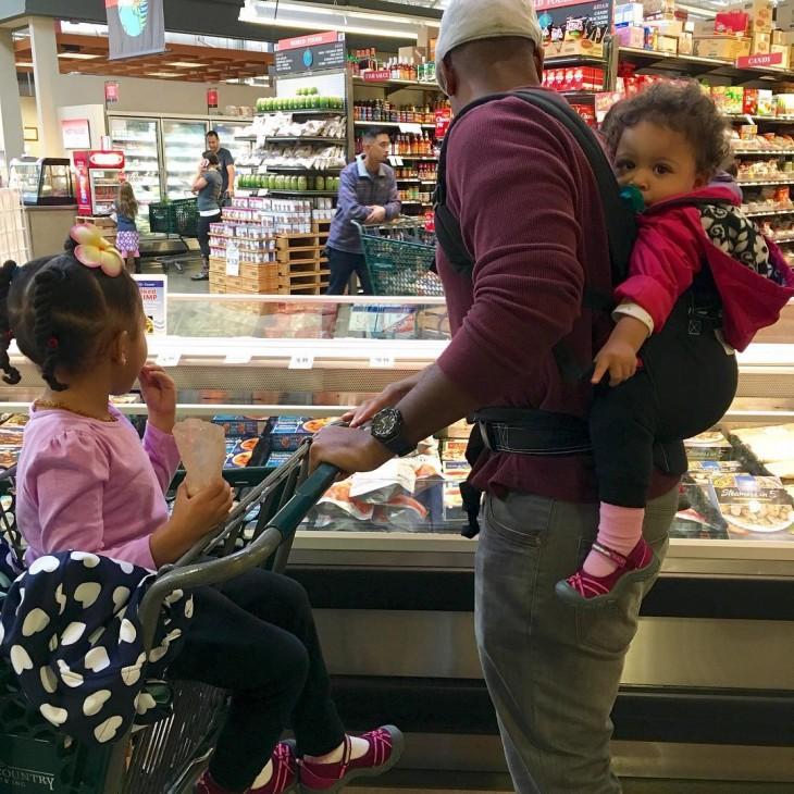 papa cuidando a sus ddos hijas mientras hacen las compras