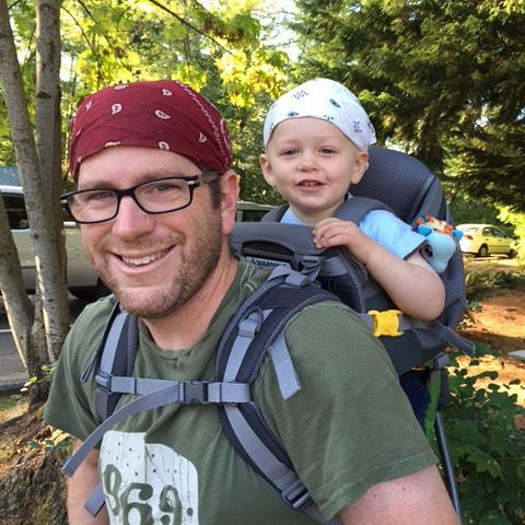 papa paseando a su hijo por las calles con un paliacate