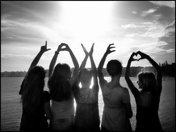 cinco amigas paniendo la palabra love y un corazon con las manos