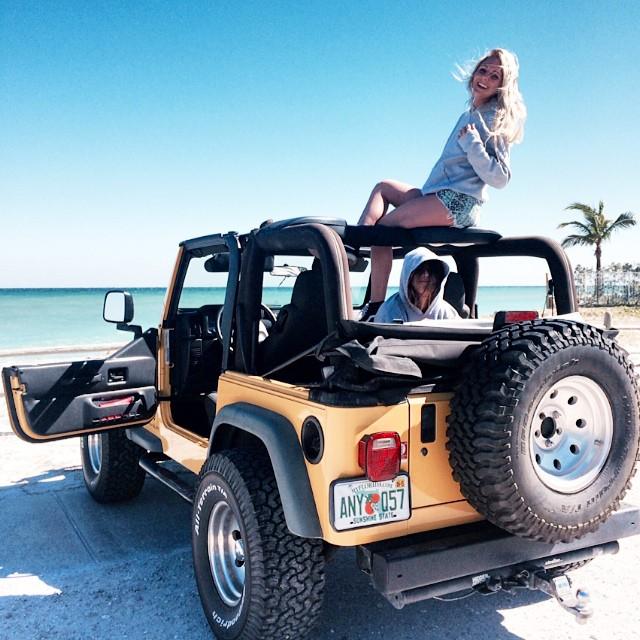 amigos disfrutando de la playa en su jeep
