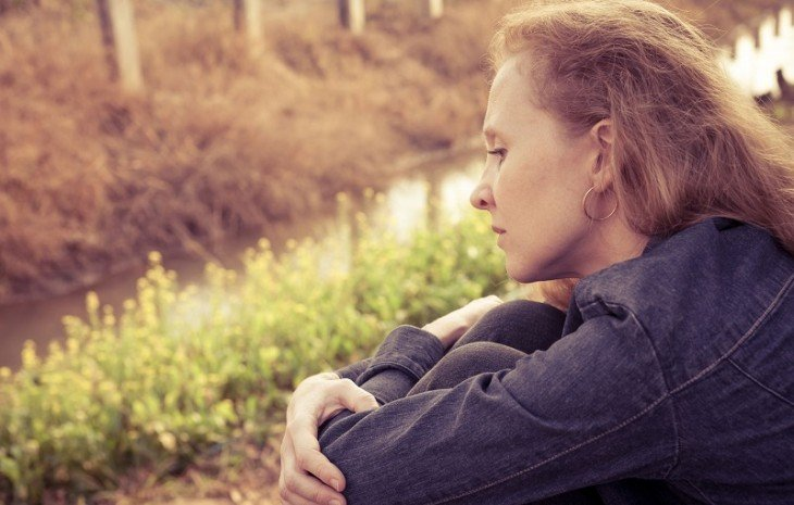 Mujer sentada abrazando su piernas cruzada de brazos muy pensativa