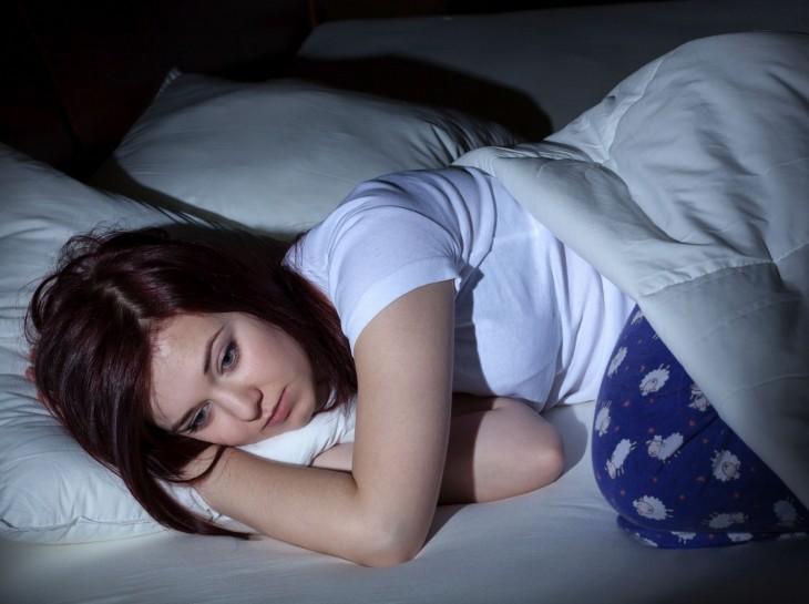 una chica recostada en su cama a media noche despierta