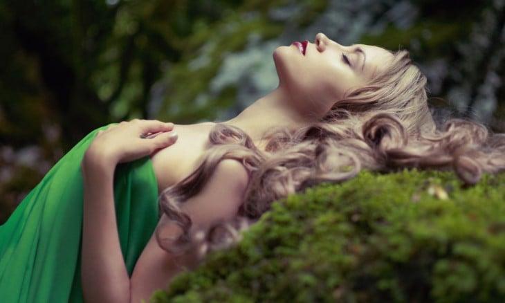 Una chica acostada sobre una roca mirando hacia arriba relajada y con los ojos cerrados