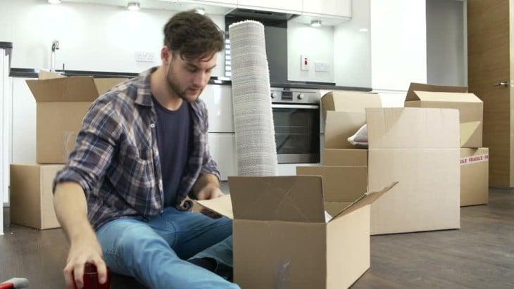 un chico rodeado de cajas en un casa solo